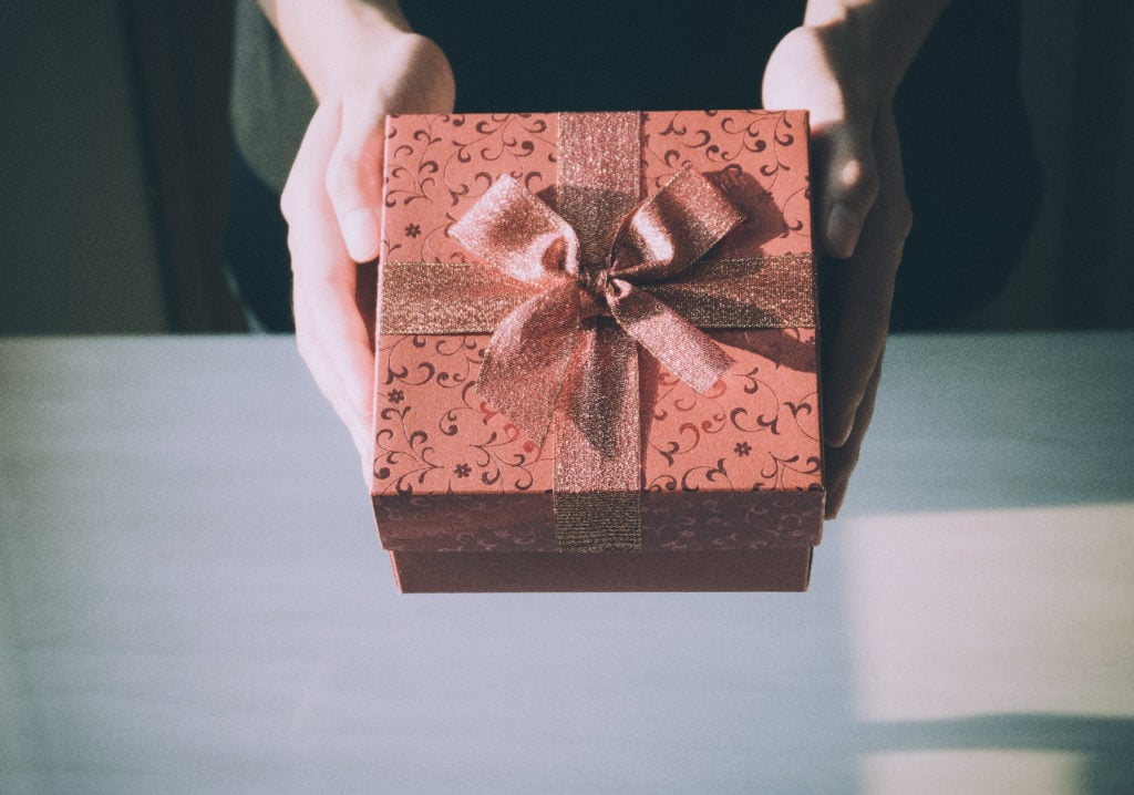 Close up of woman hands holding red gift box for special event