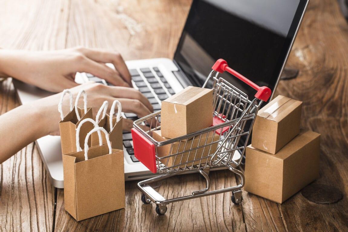 Pirkinių krepšelis, nešiojamas kompiuteris ir prekių maišeliai bei dėžutės