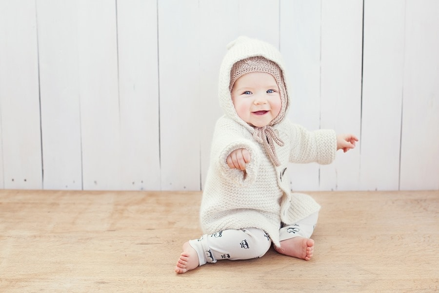Linksmas kūdikis sėdi ant grindų su Gera Bloga megztuku. Saulės Pieva Fotografija. Pirmoji prekės ženklo fotosesija.