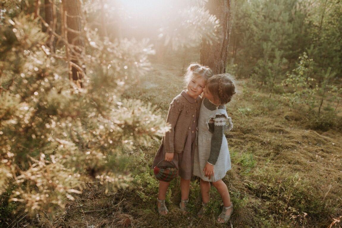 Dvi mergaitės apsikabinę prie žydinčio krūmo